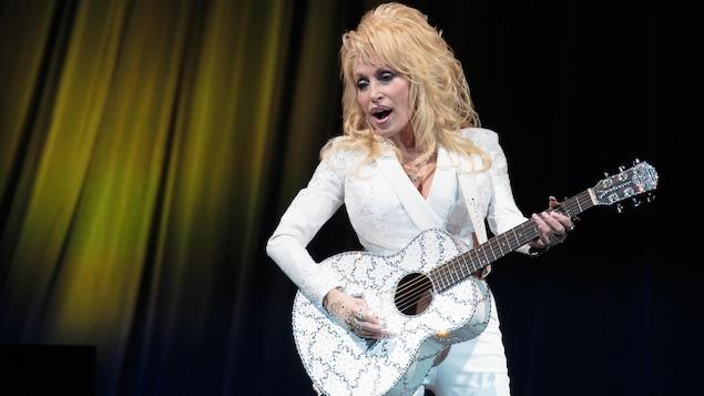 La femme chante sur scène toute habillée de blanc et joue de la guitare.