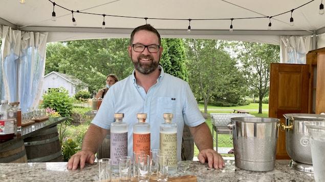 Un homme pose devant un comptoir sur lequel est posé des bouteilles et des verres.