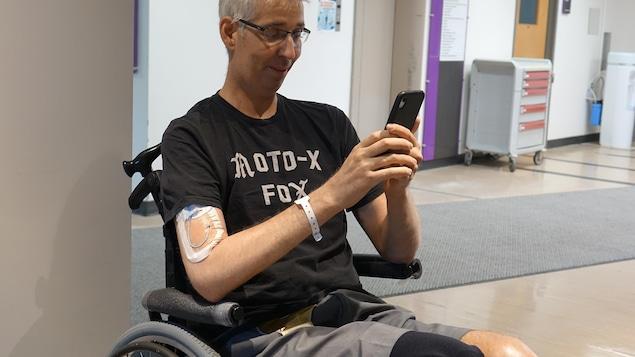 Un homme assis sur un fauteuil roulant parle au téléphone.