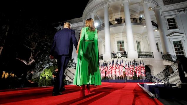 Donald Trump et Melania Trump marchent sur un tapis rouge vers la Maison-Blanche.