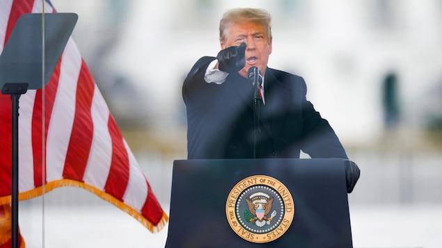 Devant un micro, Donald Trump pointe son doigt devant lui.