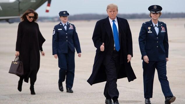 Un homme flanqué de deux femmes militaires et suivi d'une autre avec des lunettes de soleil, marche sur une piste d'atterrissage d'une base militaire.