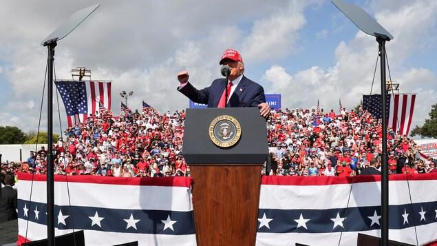 Donald Trump parle sur une scène, derrière lui se trouvent des partisans dans une estrade.