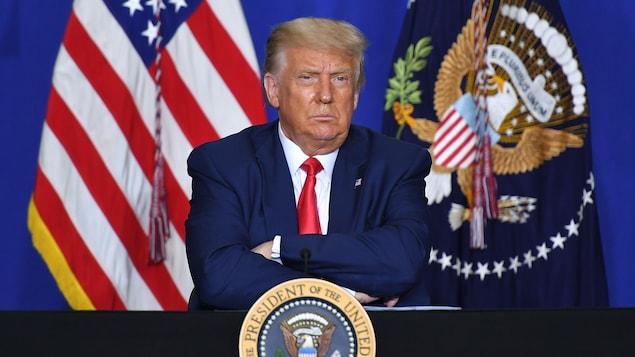 Le président, les sourcils froncés, les bras croisés, est assis.
