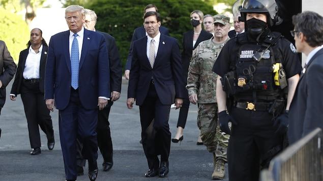 Donald Trump, entouré de plusieurs personnes, marche à l'extérieur.