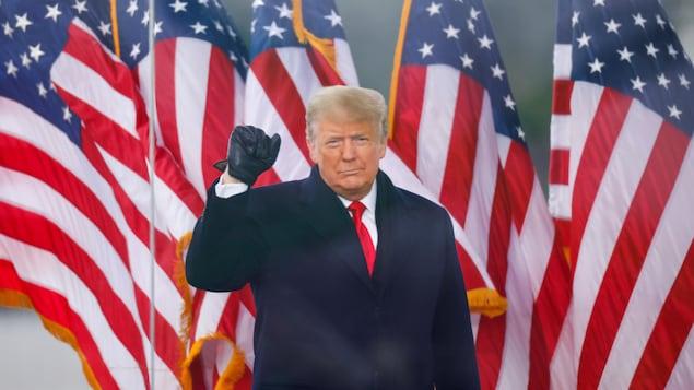 Donald Trump a le poing fermé levé en l'air.