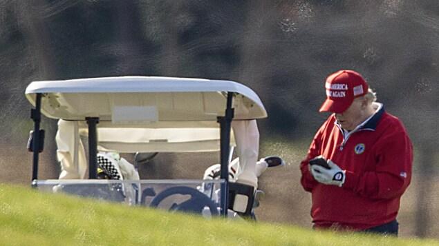 Donald Trump, au golf, penché sur son cellulaire.