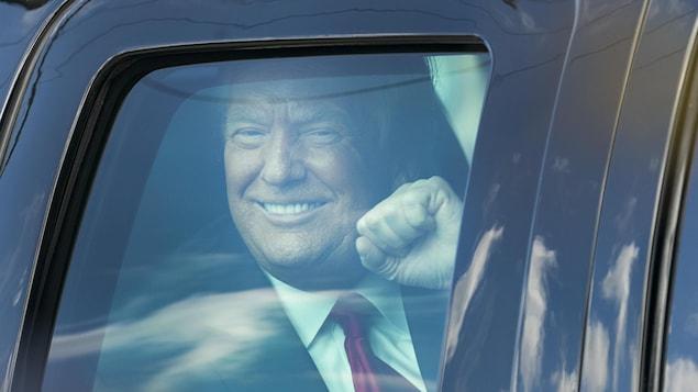 Donald Trump, souriant et le poing levé, vu à travers la vitre d'une voiture à son arrivée à Mar-a-Lago, en Floride.