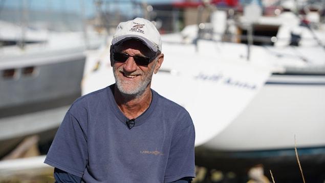 Eudore Gaudet devant son voilier aux Îles-de-la-Madeleine.