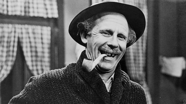 Le père Gédéon Plouffe (Doris Lussier), souriant, une pipe à la bouche.