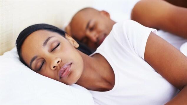 Une femme et un homme dorment côte à côte dans le même lit.