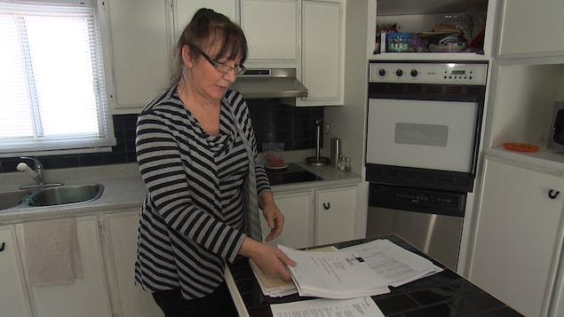 Sylvie Aubry montre le nombreux documents qu'elle doit remplir pour obtenir une allocation pour enfants lourdement handicapés.
