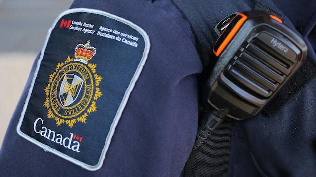 On voit la manche de l'uniforme d'un agent frontalier.