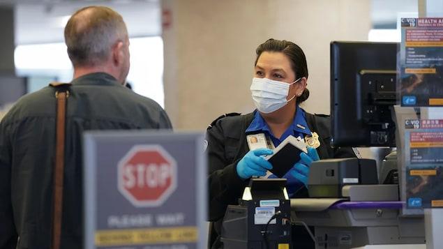 Une douanière américaine qui porte un masque regarde un voyageur.