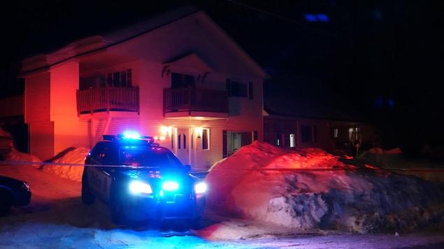 Une voiture de police stationnée dans l'entrée d'une maison à deux étages, la nuit.