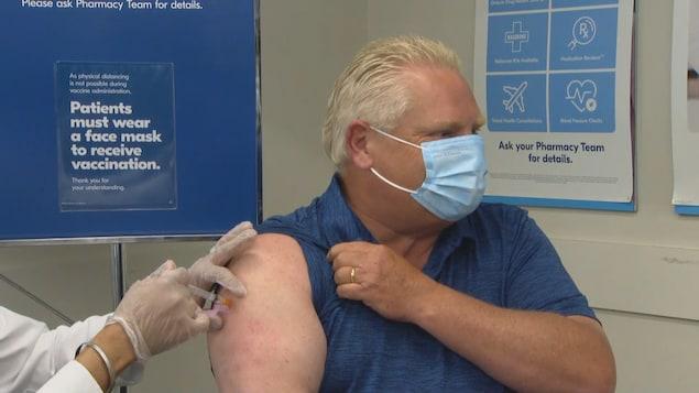 Doug Ford se fait injecter le vaccin dans l'épaule.