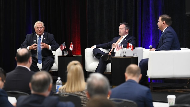 Le premier ministre de l'Ontario, Doug Ford en discussion avec le premier ministre de l'Alberta, Jason Kenney, assis sur une scène et devant des spectateurs.