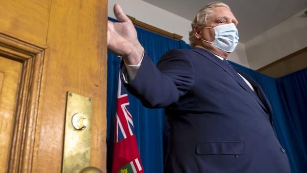 Doug Ford porte le masque et s'apprête à fermer une porte.