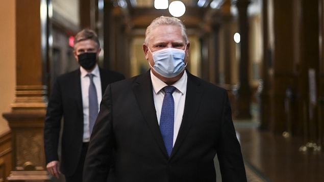 Doug Ford en compagnie de son ancien ministre des Finances, Rod Phillips, marchent dans un corridor à Queen's Park.