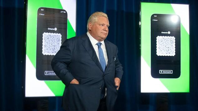 Nasa entablado si Doug Ford at nasa likod niya ang screen na nagpapakita ng vaccine verification app ng Ontario.