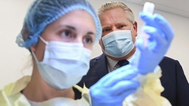 Doug Ford observe une infirmière qui s'apprête à administrer un vaccin contre la COVID-19 à Toronto.