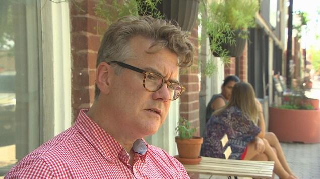 Un homme portant des lunettes et une chemise carreautée rouge et blanche est assis à la terrasse d'un café.