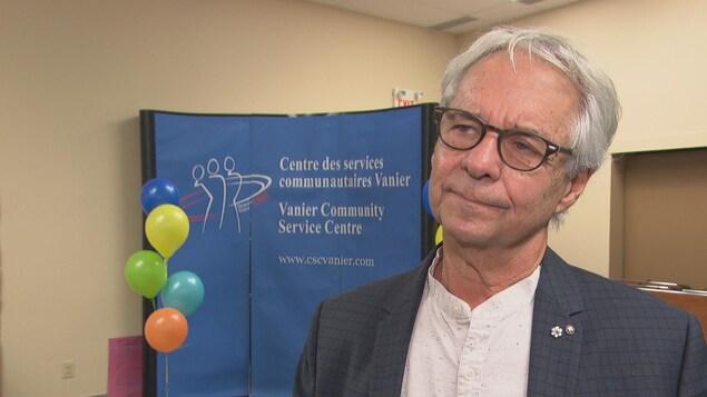 Le Dr Gilles Julien avec un paravent du Centre des services communautaires Vanier et des ballons.