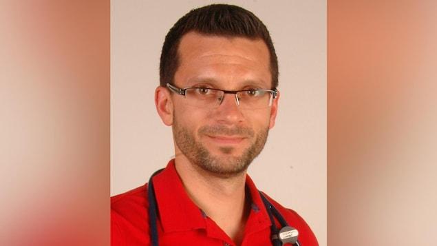 Portrait du médecin portant des lunettes et un polo rouge.