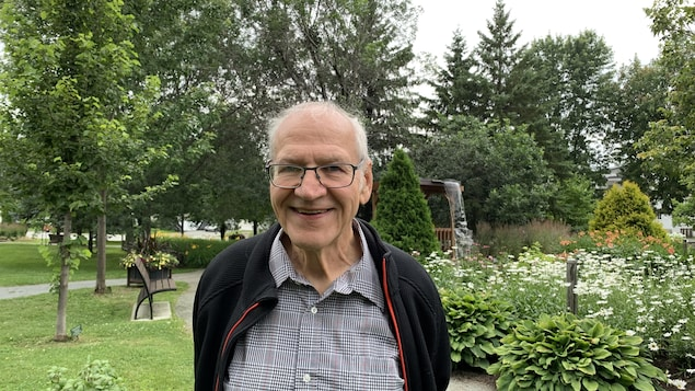 Le Dr Pierre Vincelette sourit à la caméra. Il se trouve dans un parc à Rouyn-Noranda.