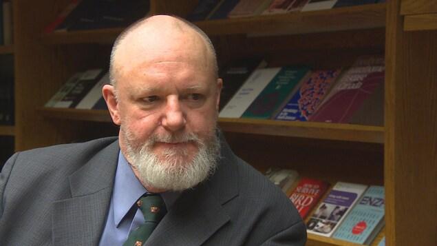 Un homme assis devant une étagère de livres.