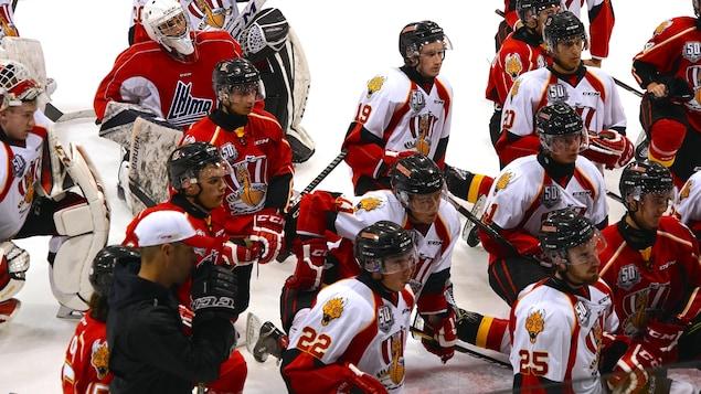 Des joueurs de hockey sur la glace écoutent les propos de leur entraîneurs