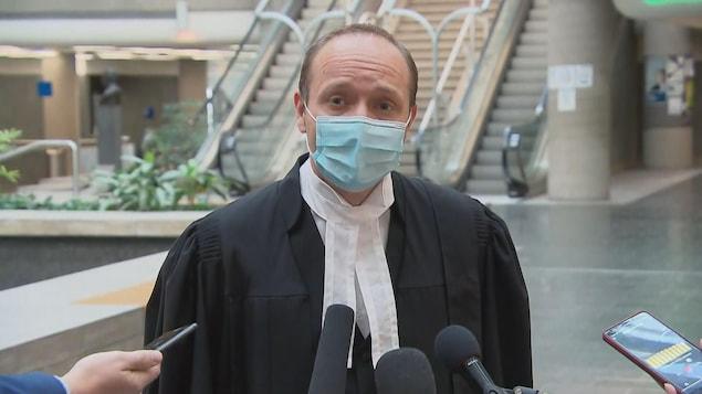 Me Godin porte un masque et s'adresse aux médias dans la cour centrale du palais de justice de Québec.