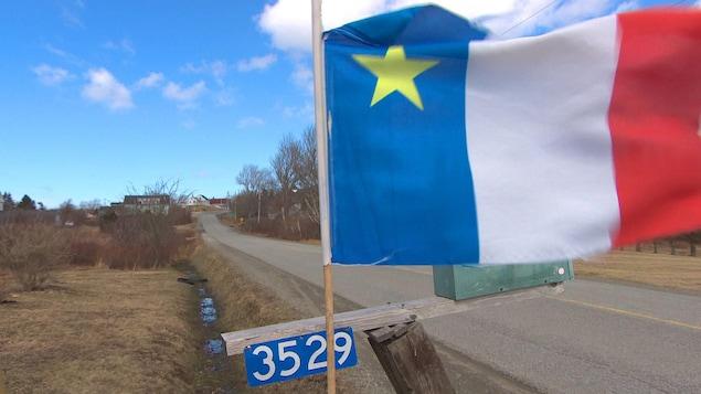 Drapeau de l'Acadie fixé à une boîte aux lettres en bordure d'une route.
