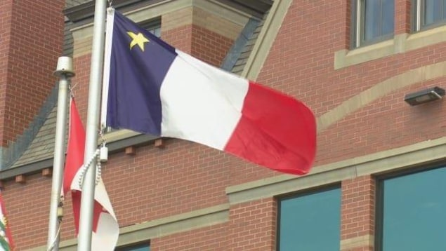 Le drapeau de l'Acadie flotte au sommet de son mât