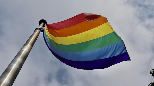 Le drapeau arc-en-ciel flotte au vent.