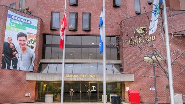 Les drapeaux de la Ville de Gatineau, du Québec et du Canada en berne devant la Maison du citoyen.