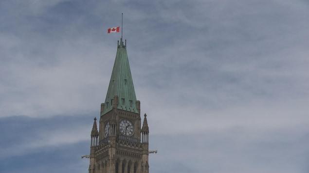 Una bandera canadiense a media altura en el edificio del Parlamento de Canadá.