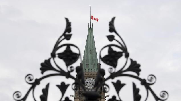 Le drapeau canadien en berne sur le Parlement, vu à travers la grille d'entrée.