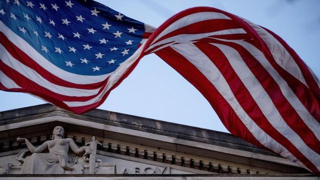 Un drapeau américain flottant devant le sommet d'un édifice.