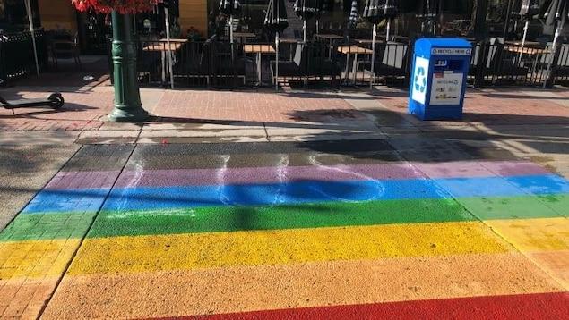 Le mot « Lust » ou luxure est écrit sur le passage pour piétons arc-en-ciel peint à une intersection du centre-ville de Calgary.