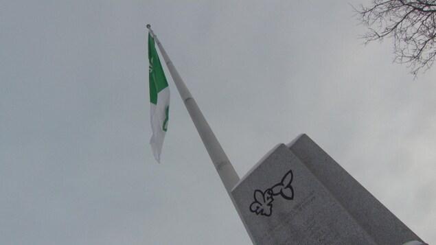 Le drapeau franco-ontarien flotte au-dessus d'un petit monument.