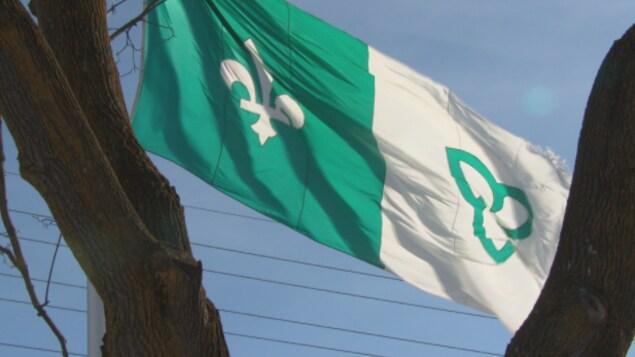 Un drapeau franco-ontarien entre deux arbres.