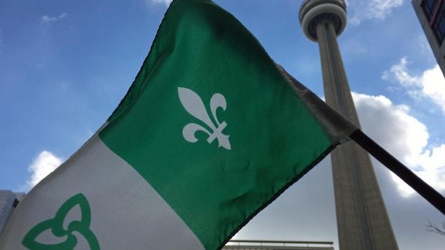 Photo d'un drapeau franco-ontarien devant la tour CN à Toronto