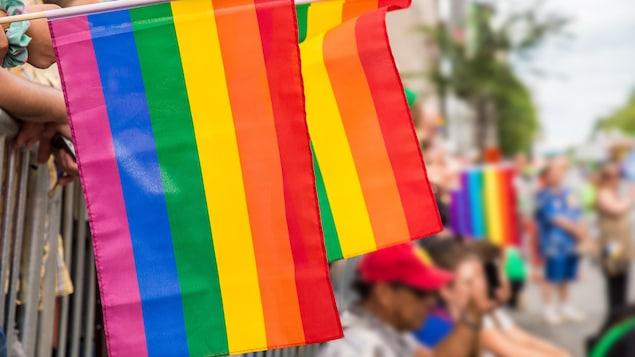 Des drapeaux gais pendent le long des clôtures lors du défilé de la fierté, à Montréal.