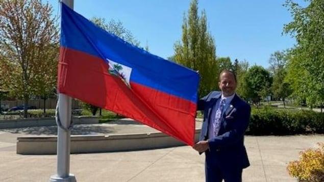 Le maire Jim Diodati tient le drapeau haïtien en souriant