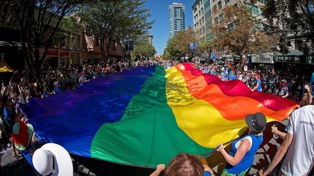 Un immense drapeau de la fierté est porté dans les rues du quartier West End à Vancouver lors d'un défilé.