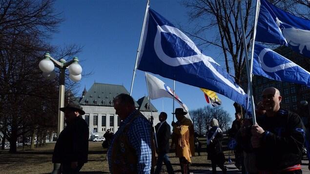 Des Métis défilent en tenant leur drapeau devant l'édifice abritant la Cour suprême du Canada, à Ottawa.