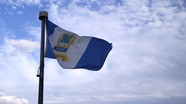 Le drapeau de la police de Trois-Rivières dans le ciel avec quelques nuages.
