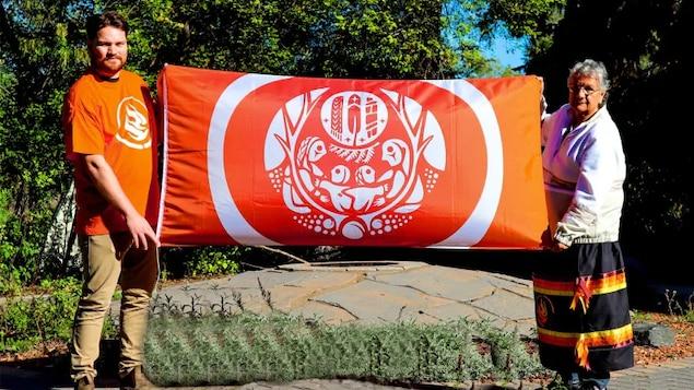 Deux personnes tiennent un drapeau orange.
