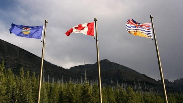 Trois drapeaux côte-à-côte dans le vent, un de l'Alberta, un du Canada et un de la Colombie-Britannique.